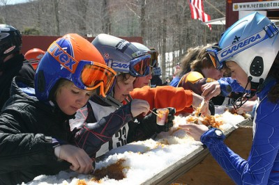 Kids eating their snow with a side of maple sugar