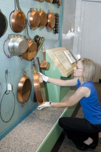 Paula Johnson installs Julia Childs copper pots to the original mapped peg board wall.