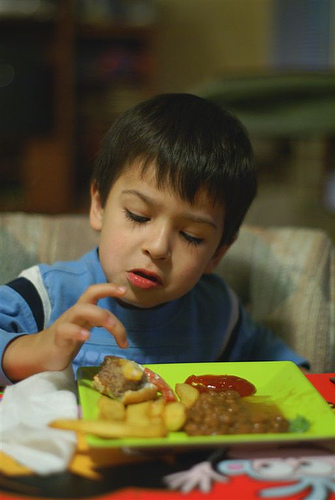 A picky eater examines his plate (Courtesy of Flickr/all in green)