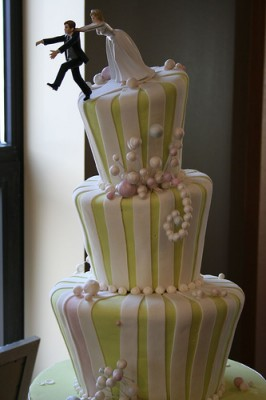 The groom cant stay away from this wedding cake. Courtesy of Flickr user tamdotcom
