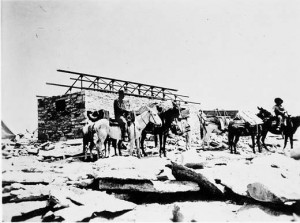 Donkeys carrying people and supplies are in front of the shelter being constructed at the Smithsonian Astrophysical Observatory at Mount Whitney, California.