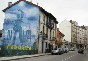 The mural above the festival plaza in Nava depicts the magnificent image of a champion cider server in action. Photo by Alastair Bland.