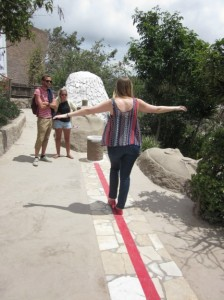 Texan tourist Amy Jones walks the true Equatorial line at the Museo Solar-Inti-Nan. Keeping one's balance is supposedly more difficult than attempting the same stunt five or 10 feet to either side of the Equator. Photo by Alastair Bland.