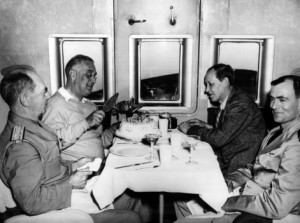 Roosevelt cuts his birthday cake in flight. Pan American pilot Howard Cone is at far right.