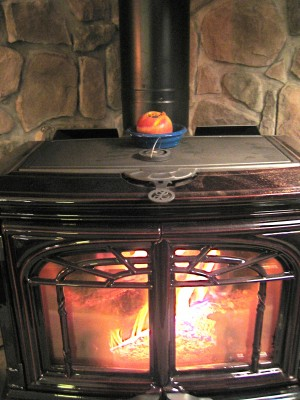 An apple bakes slowly in a schnitzer atop a wood stove. Photograph by Lisa Bramen.