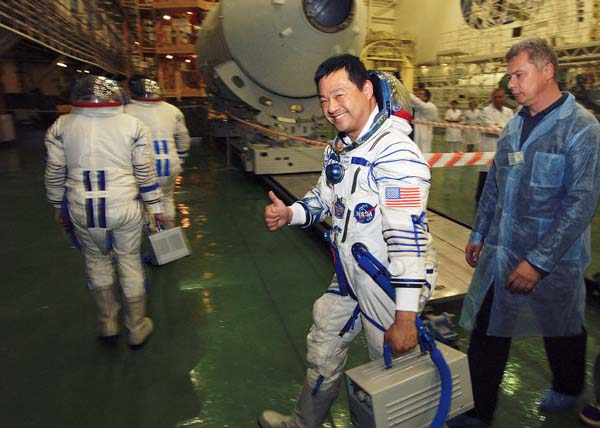 Leroy Chiao offers the universal salute on October 5, 2004, as he heads for a dress rehearsal in the Soyuz capsule that would carry him nine days later to the ISS, where he would command Expedition 10.