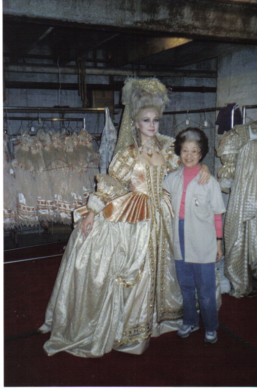 May Ishimoto, right, stands backstage with a dancer who is wearing one of her costumes.