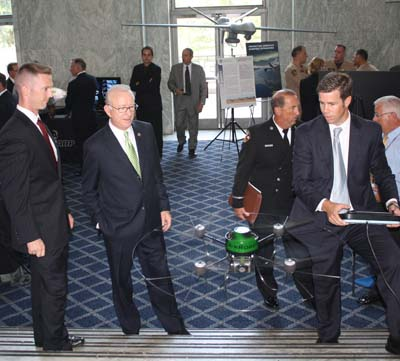 "Representative ""Buck"" McKeon, second from left, watches a demonstraton of a rotary UAV."