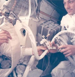 "Jack Swigert helps jury-rig the ""mailbox,"" the lithium-hydroxide cannisters needed to purge carbon dioxide from the air inside the lunar module on their trip home. Photo: NASA"