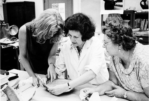 National Museum of Natural History's Anthropology Conservation Laboratory volunteer Edith Deitz (right) looking at an artifact in the laboratory with staff members.