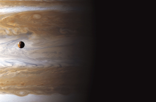 In this image, Io High Above Jupiter's Storms, Io appears near the center in the transition area between Jupiter's day and night sides. Photo copyright Michael Benson;courtesy of the Air and Space Museum.