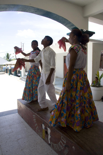 Three youths from the community of El Ciruelo, Oaxaca, perform the baile de artesa, or artesa dance. An artesa is a long, hollow wooden platform upon which barefoot dancers articulate rhythms that accompany the music. Photo by Cristina Díaz-Carrera