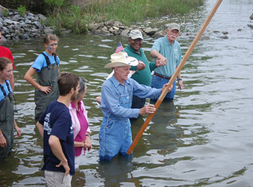 Former Maryland State Sen. Bernie Fowler, wearing coveralls and a cowboy hat, leads a group of residents into the water during a wade-in event last year. Photo courtesy of the SERC.