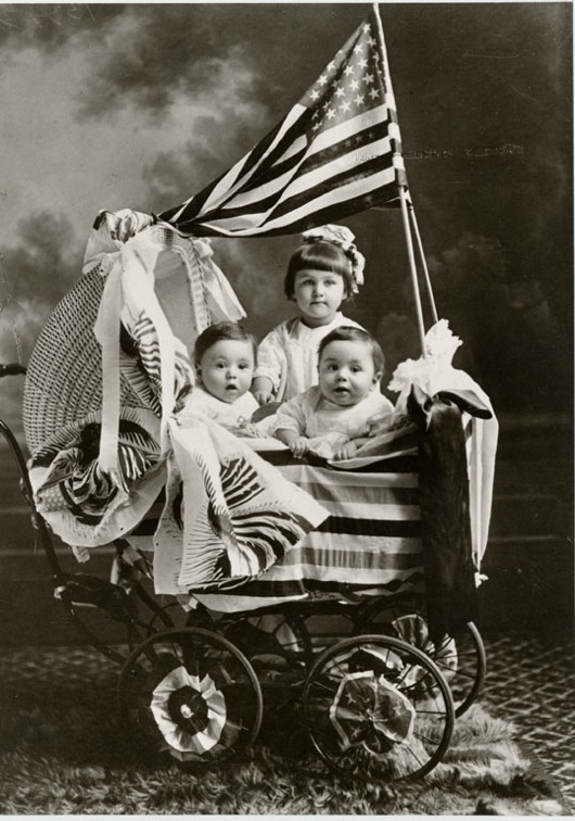 Three children in a wicker baby carriage with an American flag (ca. 1900-1920). Photographer unknown. Image courtesy of the Faris and Yamna Naff Arab-American Collection, Archives Center, National Museum of American History.