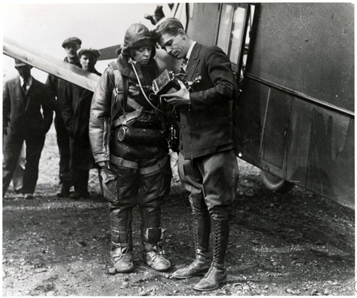 Elinor Smith Sullivan, one of America's earliest female pilots, examines a barograph with an aviation official after her 1930 record altitude flight. Photo Courtesy of the Smithsonian Institution.