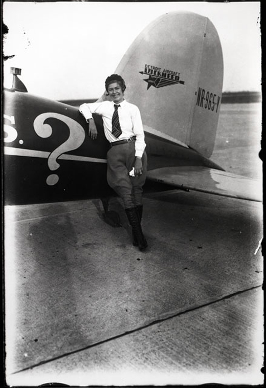 "Elinor Smith Sullivan stands next to the Lockheed Vega airplane, named ""Mrs.?"", which she purchased to fly nonstop from New York to Rome in 1930. She never made it -- but the plane was later purchased by Amelia Earhart and used for her 1935 Pacific flight. Photo Courtesy of the Rudy Arnold Collection."