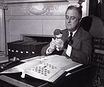 President Roosevelt set aside time in his day to study his stamp albums.