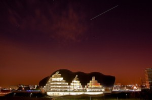 The ISS and docked Discovery pass over the Sage Gateshead in Newcastle Upon Tyne, England. (15-second exposure, courtesy of flickr user Bichologo)