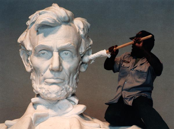 National Parks Service employee James Hudson swabs at the ear of the statue at the Lincoln Memorial in Washington, D.C. -- but surely you can come up with a better caption? -- Bettmann / Corbis