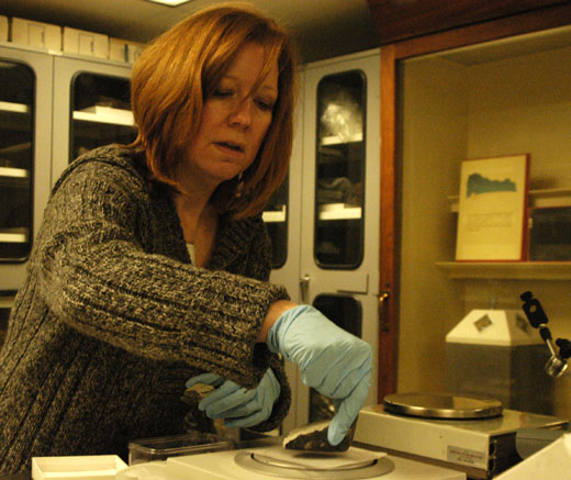"Linda Welzenbach, the manager of the Natural History Museum's meteorite collection, puts the ""Lorton"" meteorite on a scale in the collection's vault."