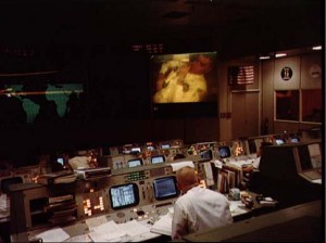Overall view of the Mission Operations Control Room (MOCR) in the Mission Control Center at Manned Spacecraft Center (MSC) during the fourth television transmission from the Apollo 13 mission in space. Eugene F. Kranz (foreground, back to camera), one of four Apollo 13 Flight Directors, views the large screen at front of MOCR. Astronaut Fred W. Haise Jr., lunar module pilot, is seen on the screen.