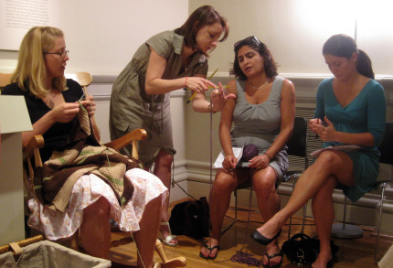 "Olga Buraya-Kefelian demonstrates to two newbie knitters how to ""cast on"" so they can begin knitting."