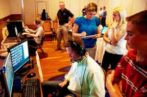 Lt. Frank Weisser (seated, foreground), the real Blue Angel #6 pilot, flies virtual #6, as Lt. Amy Tomlinson and flight surgeon Lt. Johannah Valentine note his performance.