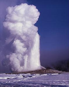 A  geyser erupts against a background of snow. Photograph by JR Douglass, National Park Service