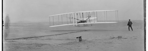 Orville Wright at controls of the Wright Flyer and Wilbur running alongside at Kitty Hawk, 1903. Photo: Library of Congress