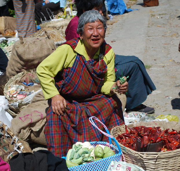 A woman sells hot peppers and other home-grown greenery at a market in Bhutan. Photo: Amy Kotkin