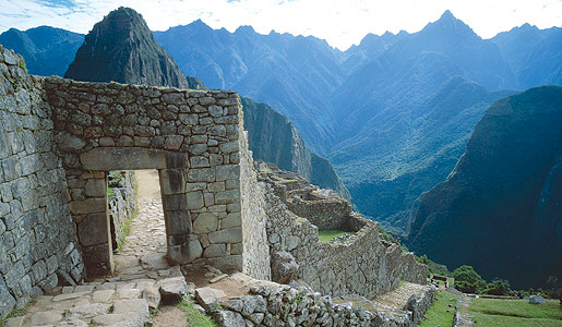 A stone archway of Machu Picchu with the Andes in the background