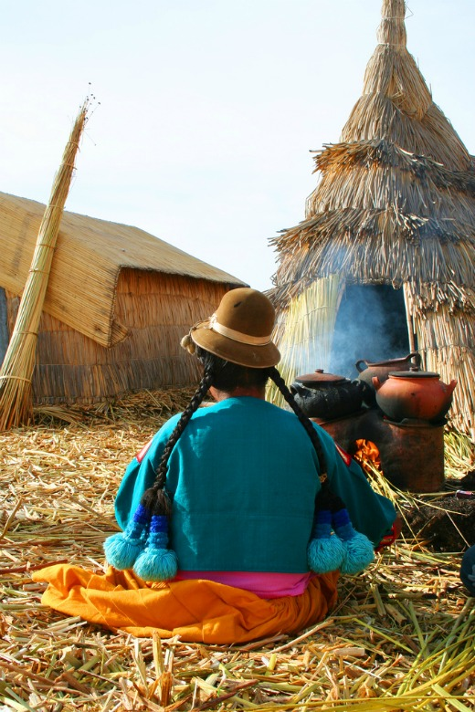 Woman cooking on Uros Island, Lake Titicaca, Peru
