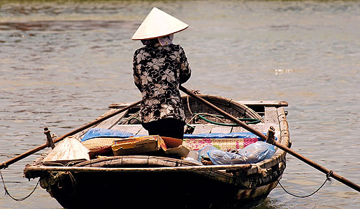 A Vietnamese woman traveling by boat in Hoi An.